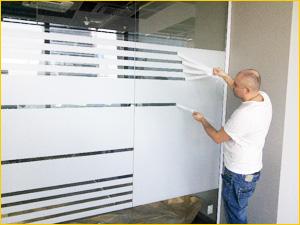 Процесс тонирования стеклянных перегородок в офисе